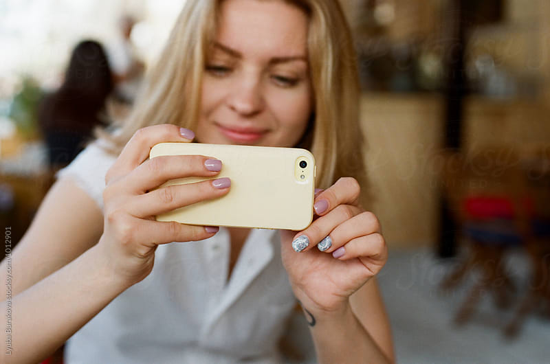 Young woman taking photo with a phone by Lyuba Burakova for Stocksy United