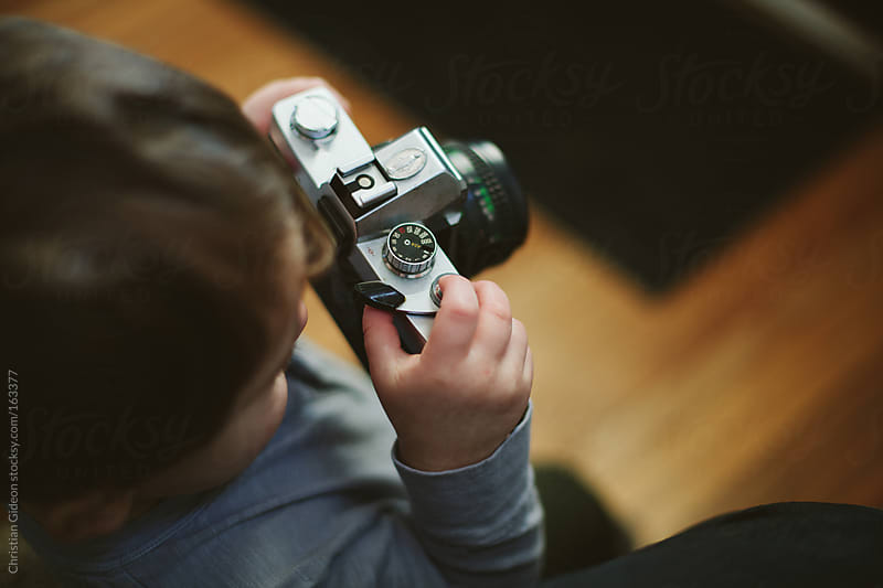 Little Boy playing with vintage film camera by Christian Gideon for Stocksy United