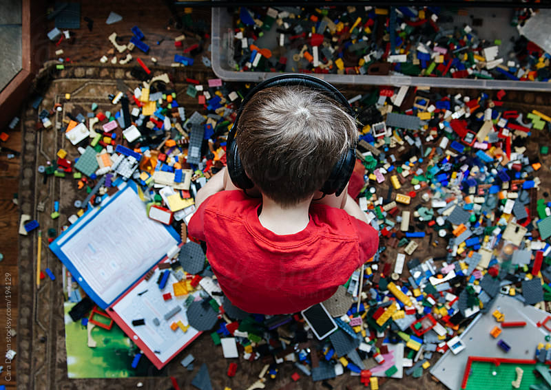 Boy listens to music as he sits on the floor at home surrounded by his toys and books by Cara Dolan for Stocksy United