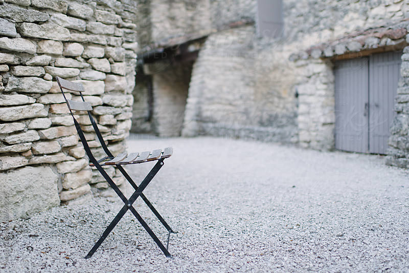 Empty chair against stone wall by Preappy for Stocksy United