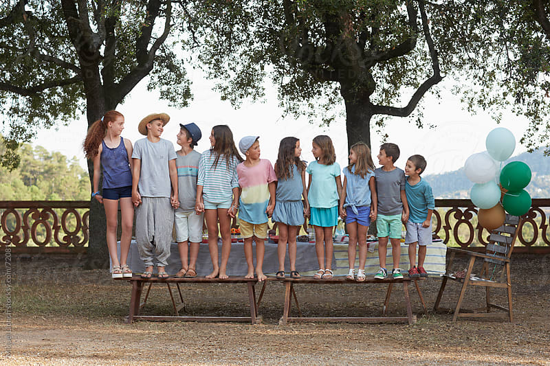 Group portrait of ten children holding hands at an outdoors party by Miquel Llonch for Stocksy United