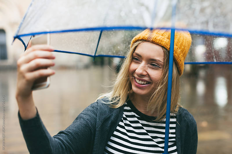 Smiling blonde woman taking a selfie on the street in a rainy day. by BONNINSTUDIO for Stocksy United