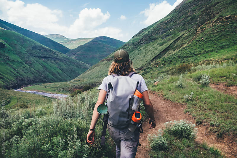 hiker outdoorsman hiking on a mountain path in the mountains overlooking a valley by Micky Wiswedel for Stocksy United