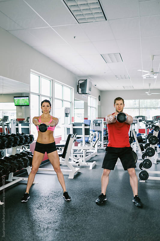 Couple working out together with kettlebell  in the gym  by Suprijono Suharjoto for Stocksy United