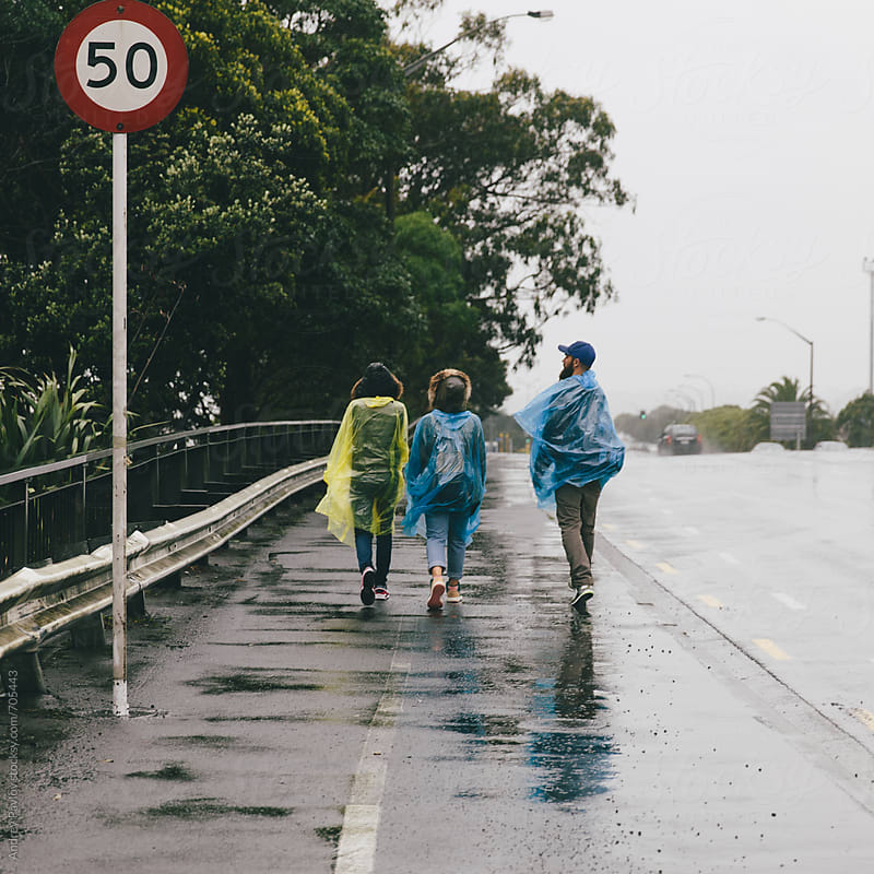 Group of friends walking at rainy weather by Andrey Pavlov for Stocksy United