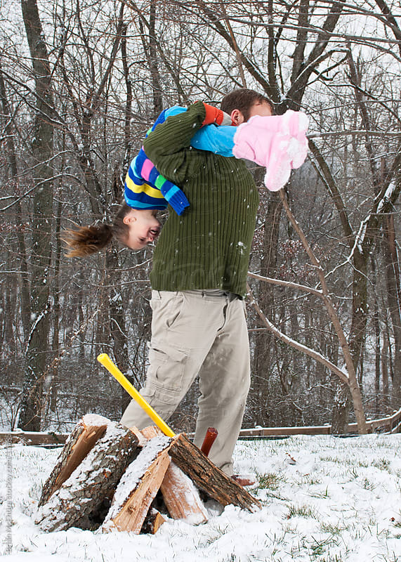 Splitting Firewood: Horseplay When Daughter Interrupts Chores by Brian McEntire for Stocksy United