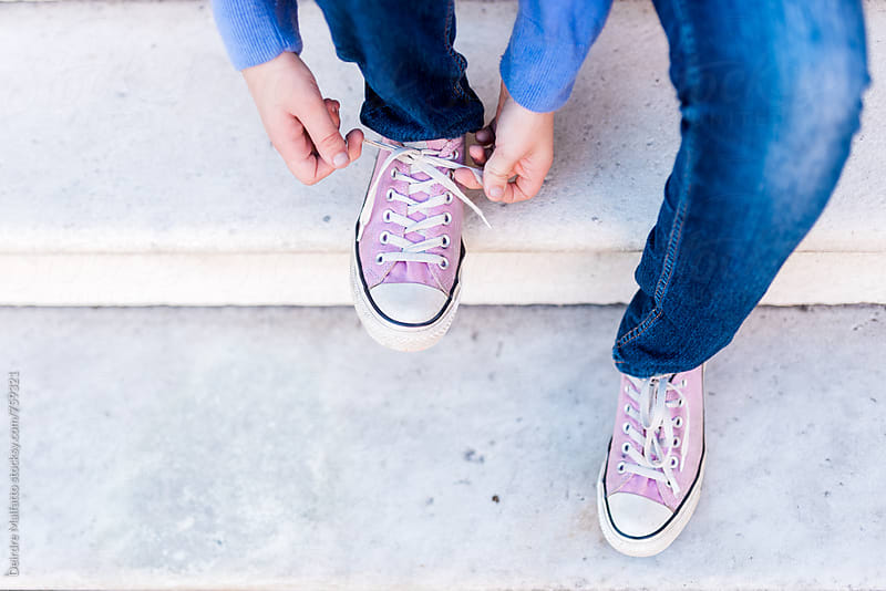 girl tying her shoelaces, from above by Deirdre Malfatto for Stocksy United