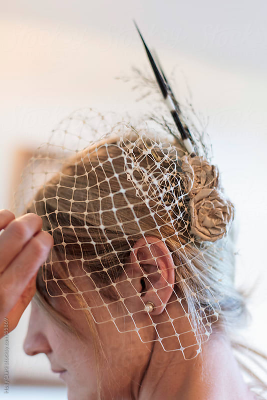 The profile of a beautiful woman adjusting the veil of her headpiece. by Holly Clark for Stocksy United