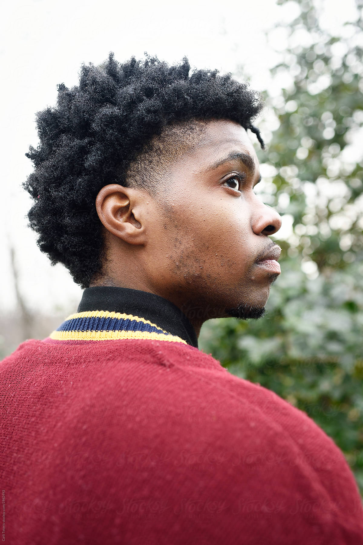 Side View Of A Young Man In A Red Sweater With A Modern Hair Style