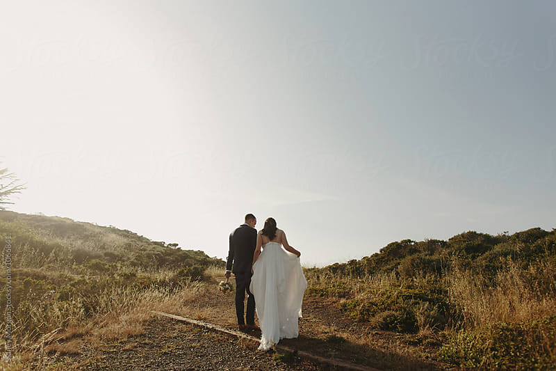Bride and Groom Walking up Hill by Sidney Morgan for Stocksy United