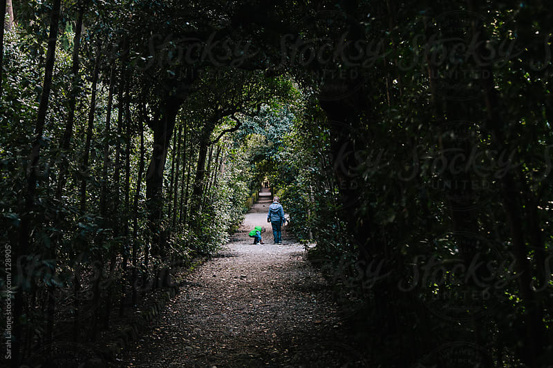 children in a vine-covered arched tunnel in a garden by Sarah Lalone for Stocksy United