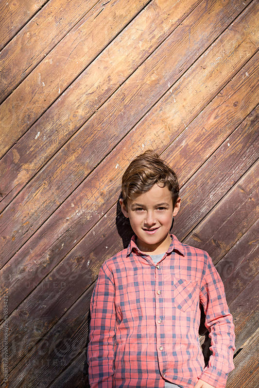 Boy on a wooden background. by Dejan Ristovski for Stocksy United