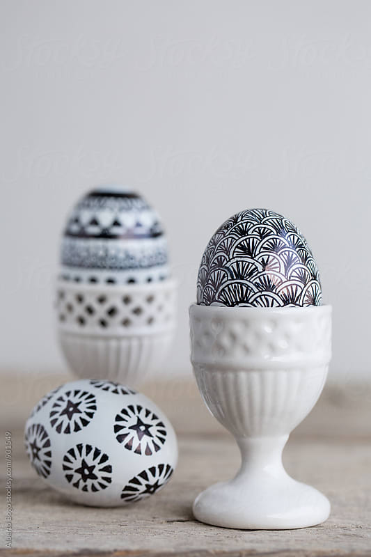 Easter eggs with handmade decoration in egg cup by Alberto Bogo for Stocksy United