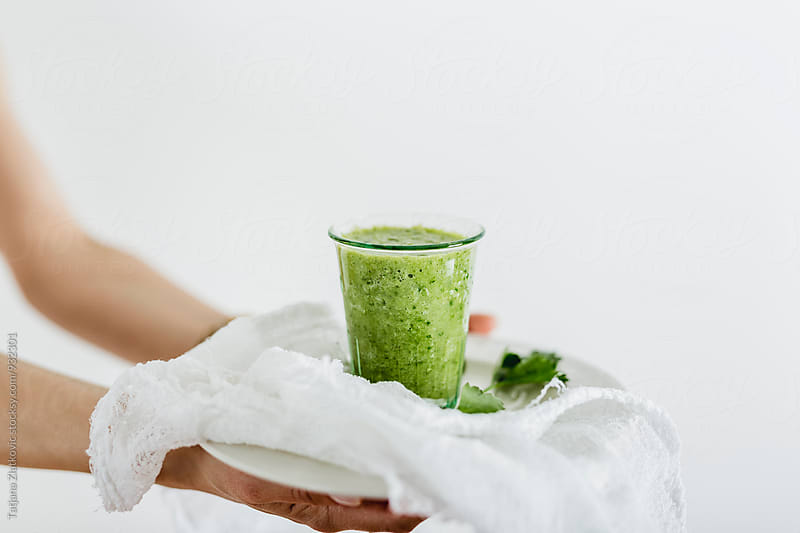 Hands holding green smoothie by Tatjana Ristanic for Stocksy United