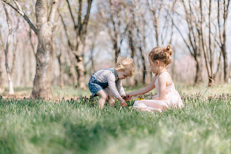 two little girls playing outside beneath flowering trees in spring by Meaghan Curry for Stocksy United