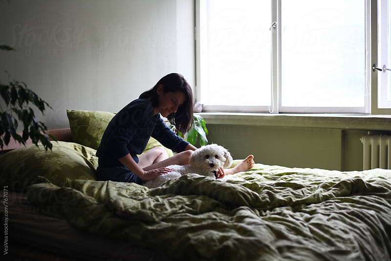 Woman petting her small white dog on the bed  by Marija Mandic for Stocksy United