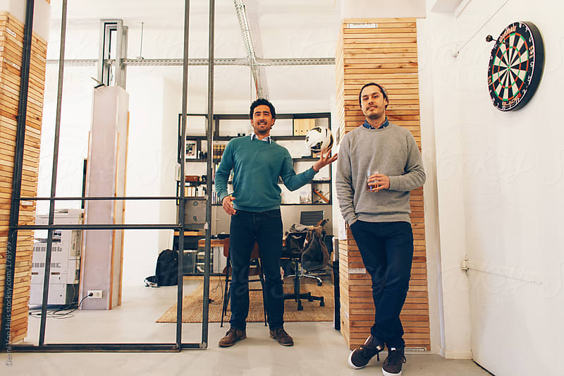 Two entrepreneurs happy at work in their own office. by Denni Van Huis for Stocksy United