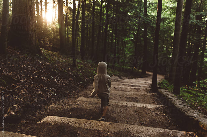 Child hiking though woods by Maria Manco for Stocksy United