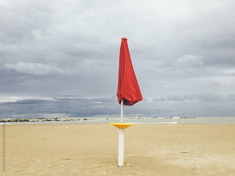red beach umbrella by Tommaso Tuzj for Stocksy United