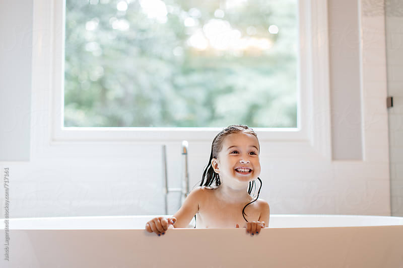 A happy young girl sitting in a bathtub by Jakob for Stocksy United