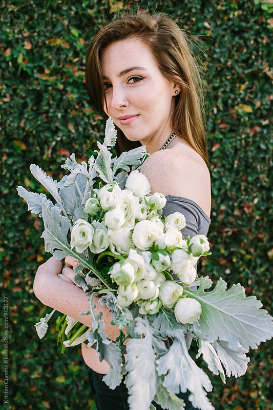 A woman holding a beautiful bouquet of white ranunculus.  by Kristen Curette Hines for Stocksy United
