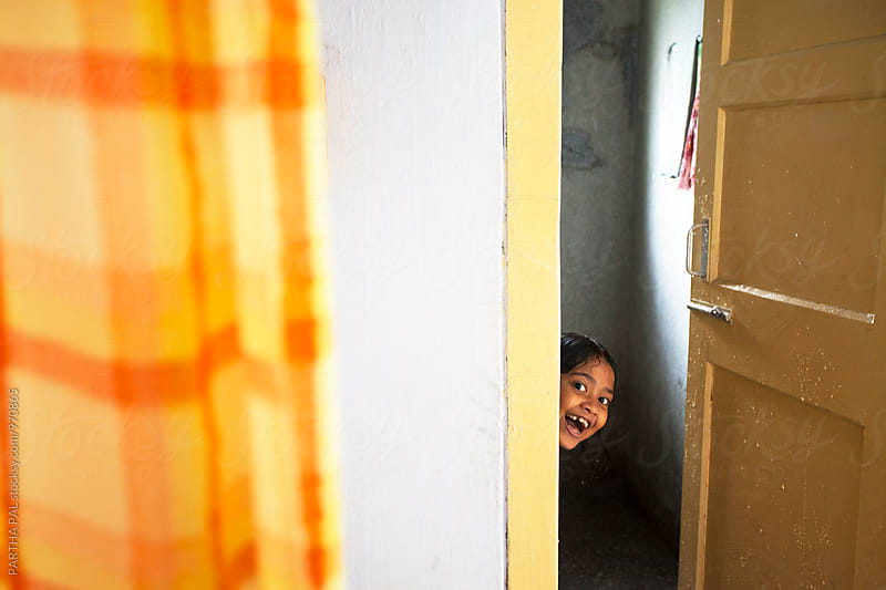 A little girl peeping throuh a door by PARTHA PAL for Stocksy United