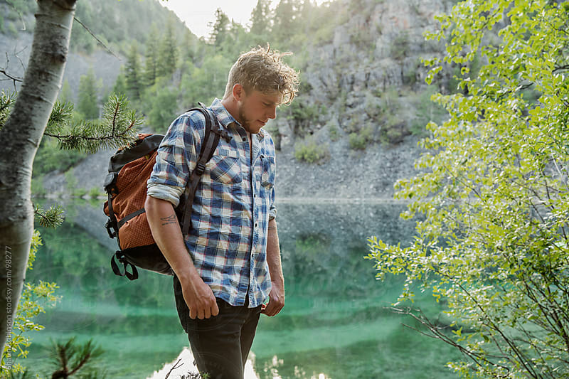 A young man standing by a lake in the woods by Shaun Robinson for Stocksy United