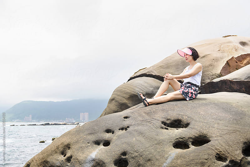 Side view of smiling woman on rock near sea by Lawren Lu for Stocksy United
