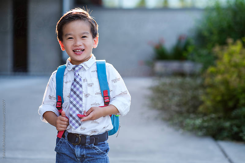 Back to school: Happy Asian kid carrying a backpack in school by Suprijono Suharjoto for Stocksy United