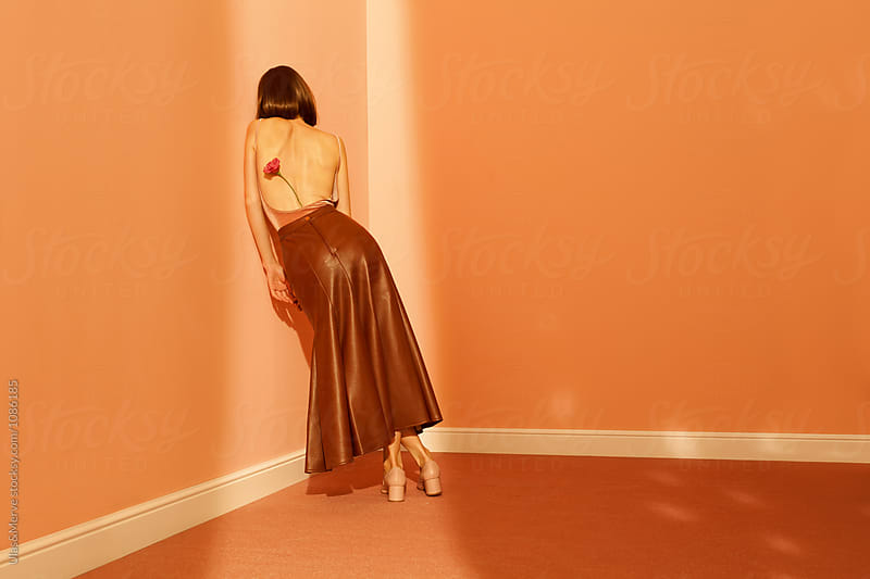 woman with long leather skirt leaning against a wall by Ulaş and Merve for Stocksy United