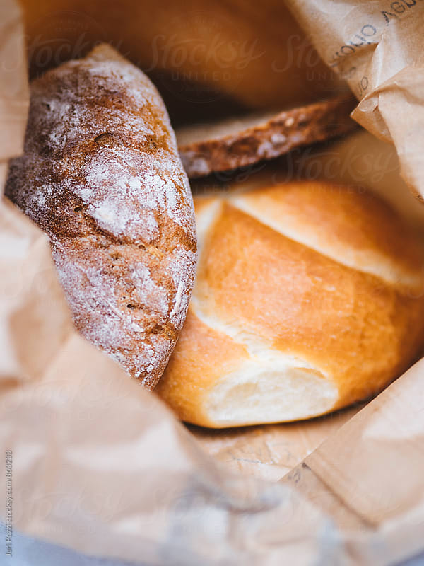 assorted bread in a paper bag by Juri Pozzi for Stocksy United