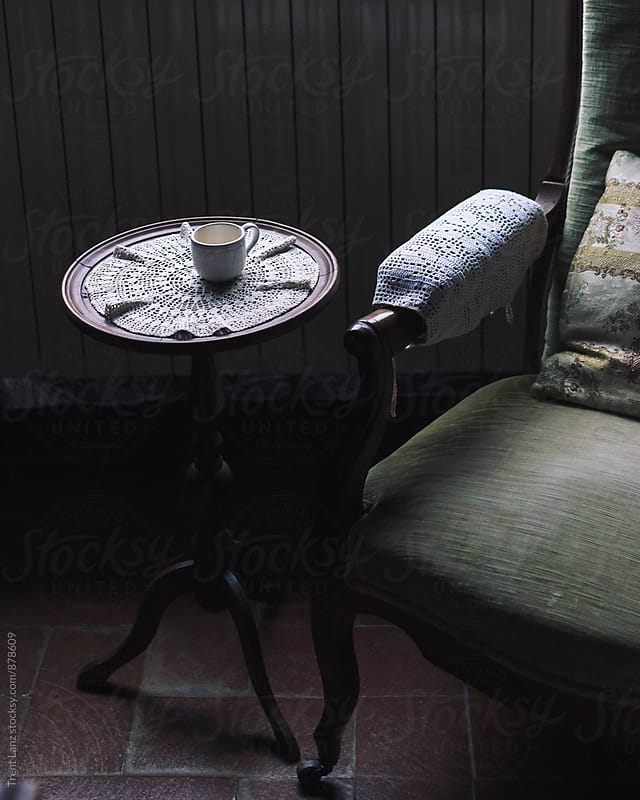Vintage armchair and coffee table with empty cup by Trent Lanz for Stocksy United