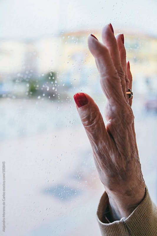 Senior woman hand with red painted nails on a window. Closeup by Alejandro Moreno de Carlos for Stocksy United