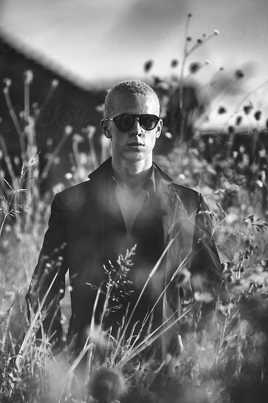 blond young man with dark glasses, dressed in a black ,sunset on the field by Igor Madjinca for Stocksy United