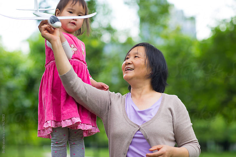 happy senior woman with her granddaughter outdoor by cuiyan Liu for Stocksy United