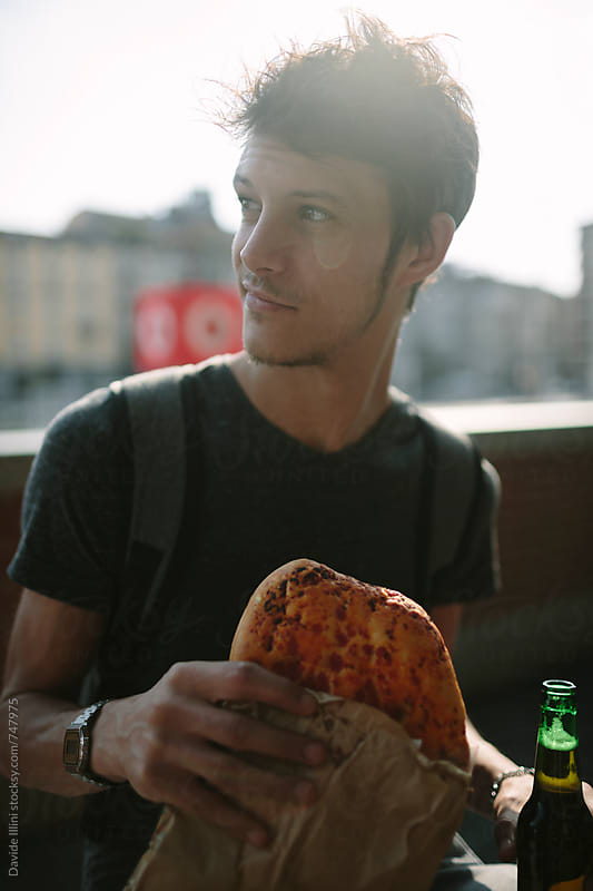 Young man eating pizza outdoors by Davide Illini for Stocksy United