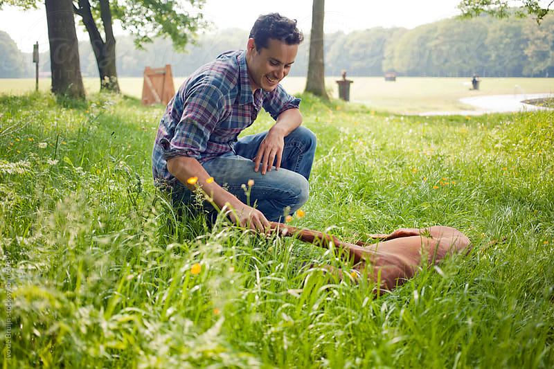 In a park, a young man and his brown haired dog are playing in the grass  by Ivo de Bruijn for Stocksy United