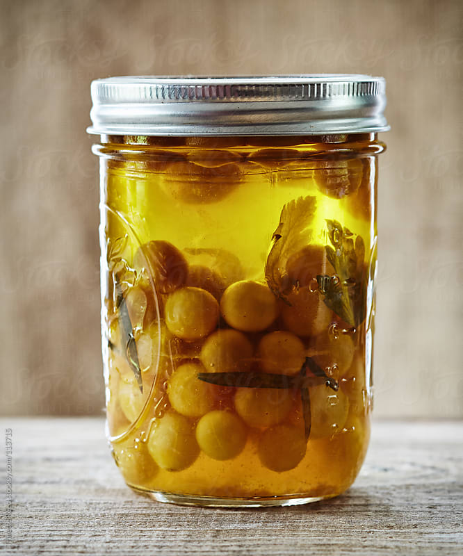 Homemade pickled olives and herbs in mason jar by Trinette Reed for Stocksy United
