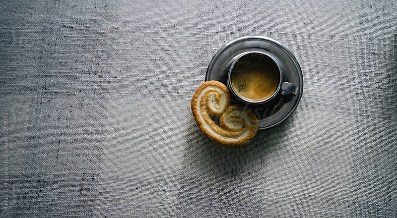 Metal cup of espresso and palmier biscuit on saucer by Manuel Chillagano for Stocksy United