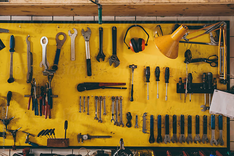 Tools organized on a yellow wall by Lior + Lone for Stocksy United