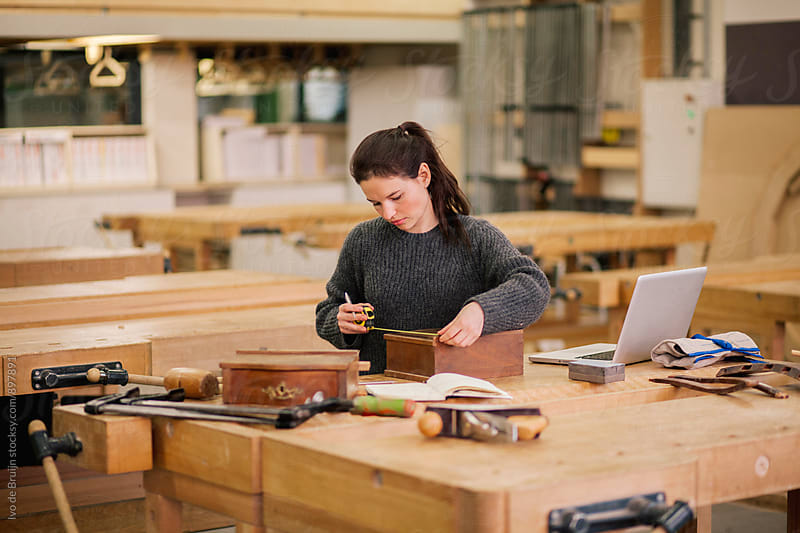 Female woodworker working on a bench, measuring a small cupboard by Ivo de Bruijn for Stocksy United