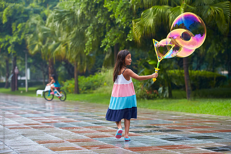 little asian girl playing bubble outdoor by Bo Bo for Stocksy United