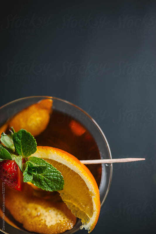 Detail overhead shot of a cocktail garnished with orange,mint and strawberry.  by Darren Muir for Stocksy United