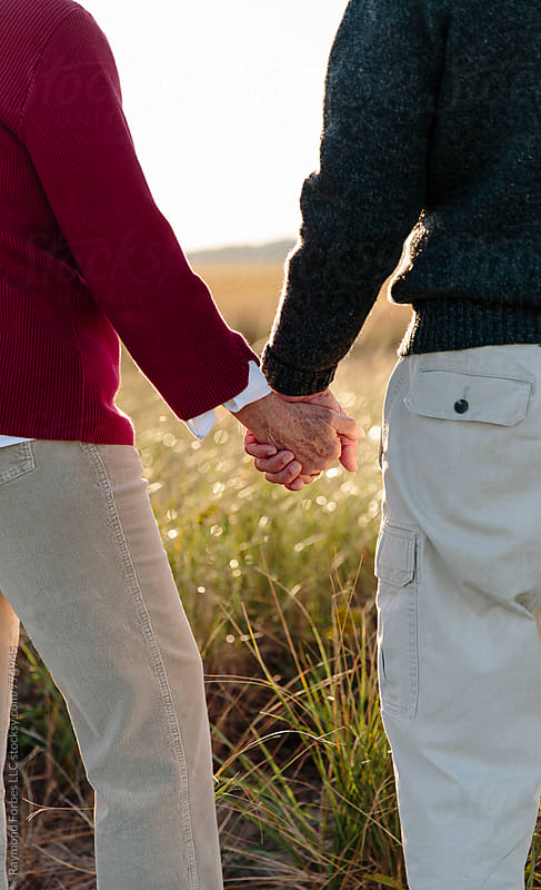 Senior Couple holding hands by Raymond Forbes LLC for Stocksy United