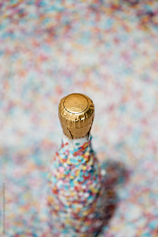 Overhead photo of a Champagne bottle covered with confetti  by Beatrix Boros for Stocksy United