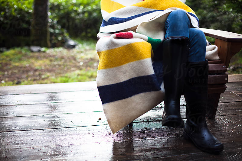 Wrapped in a blanket on the patio in the forest. by Cherish Bryck for Stocksy United
