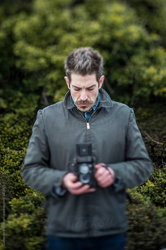 Photographer using twin lens reflex camera outdoors by Cameron Whitman for Stocksy United