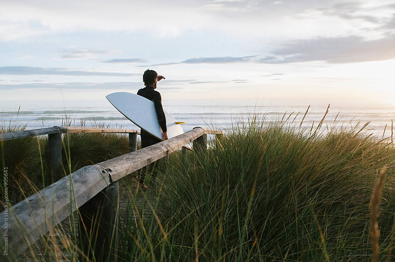 Surfer looking at waves, New Zealand. by Thomas Pickard for Stocksy United