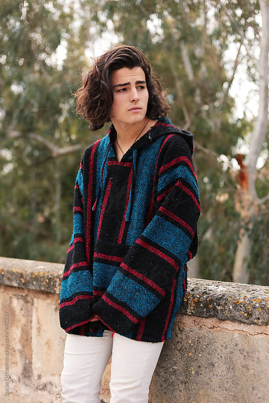 Bohemian teenage boy with long hair outdoors by Lucas Ottone for Stocksy United