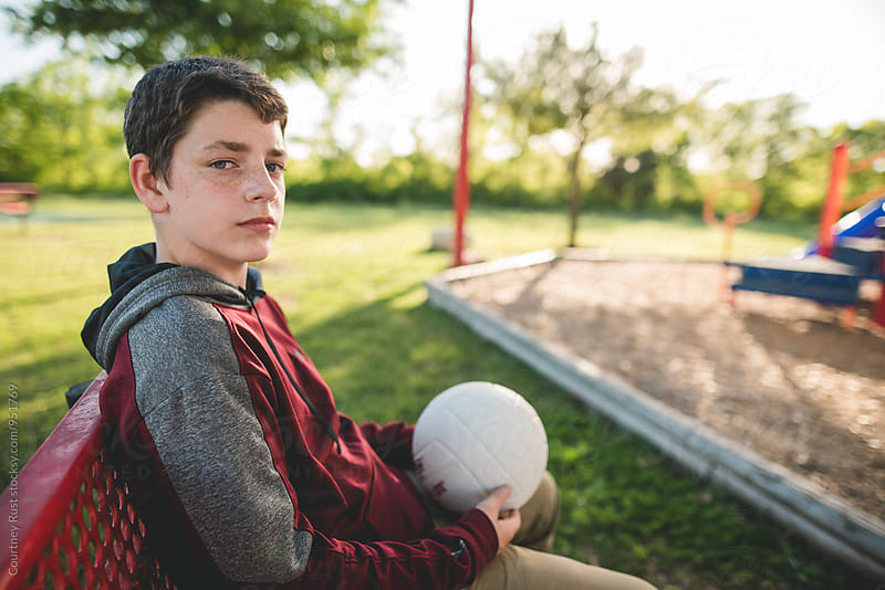 Teen boy holding a volleyball at park by Courtney Rust for Stocksy United
